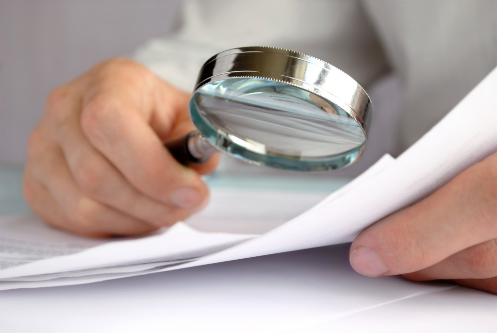 15988864 - businessman looking through a magnifying glass to documents